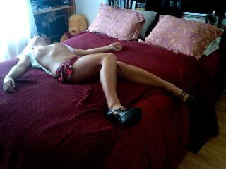 Girl in dress spreads her legs in bed