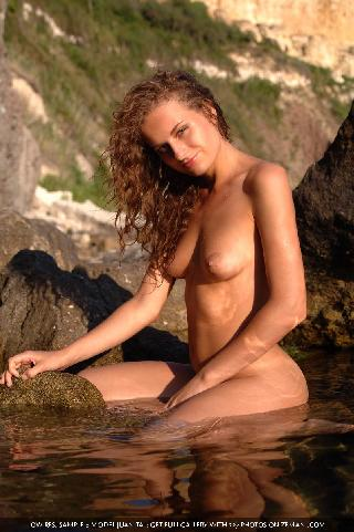 Red and curly girl sits naked on a sea stones - Juanita