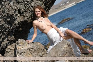 Hot red haired Ella relaxing on the beach and shows her body