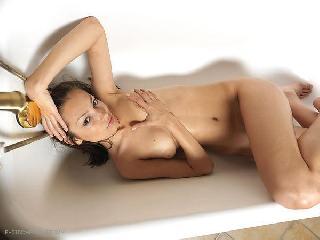 Magnificent Elvira is lying in a bathtub
