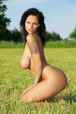 Naked Rebelde is posing on the grass