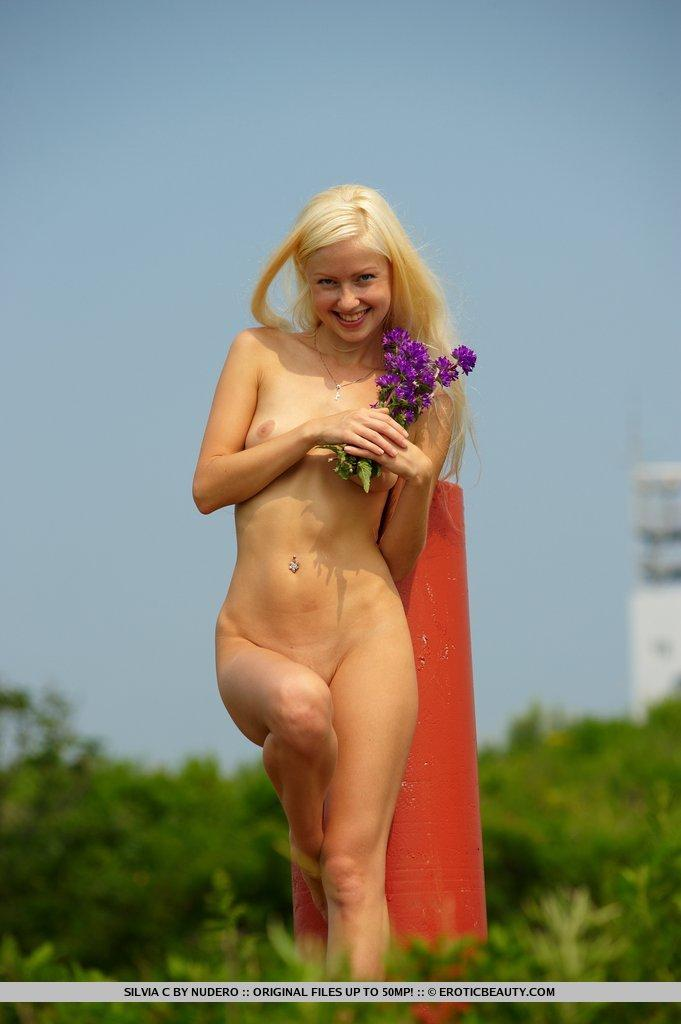 Silvia is doing striptease on the green field - 13