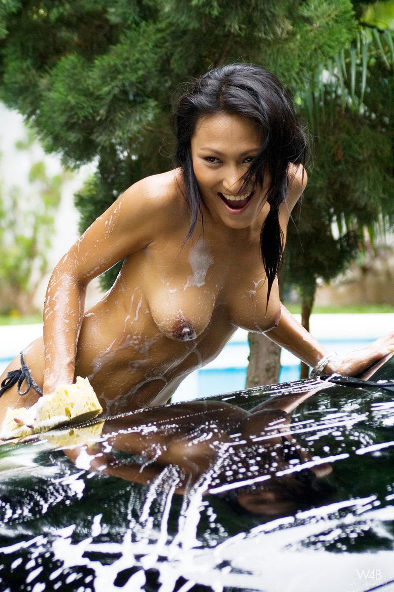 Tanned Asian is washing a car - 1