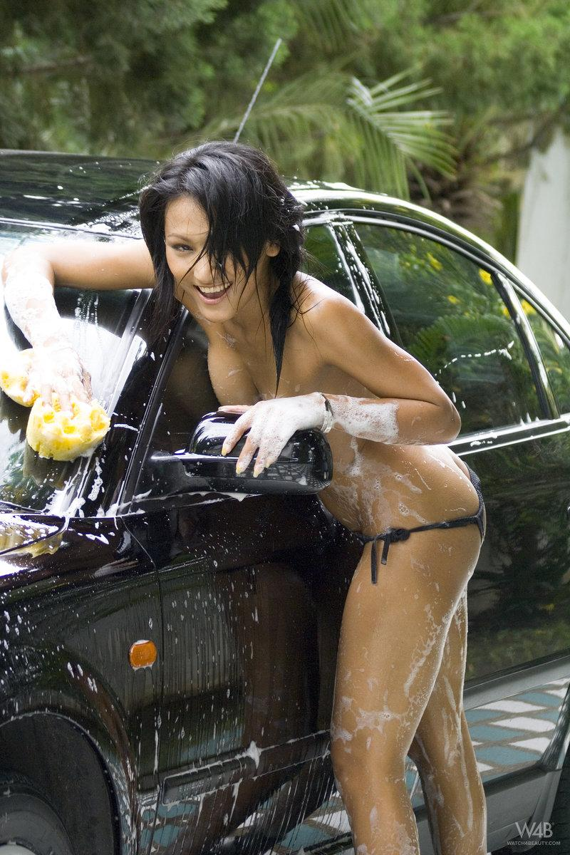 Tanned Asian is washing a car - 10