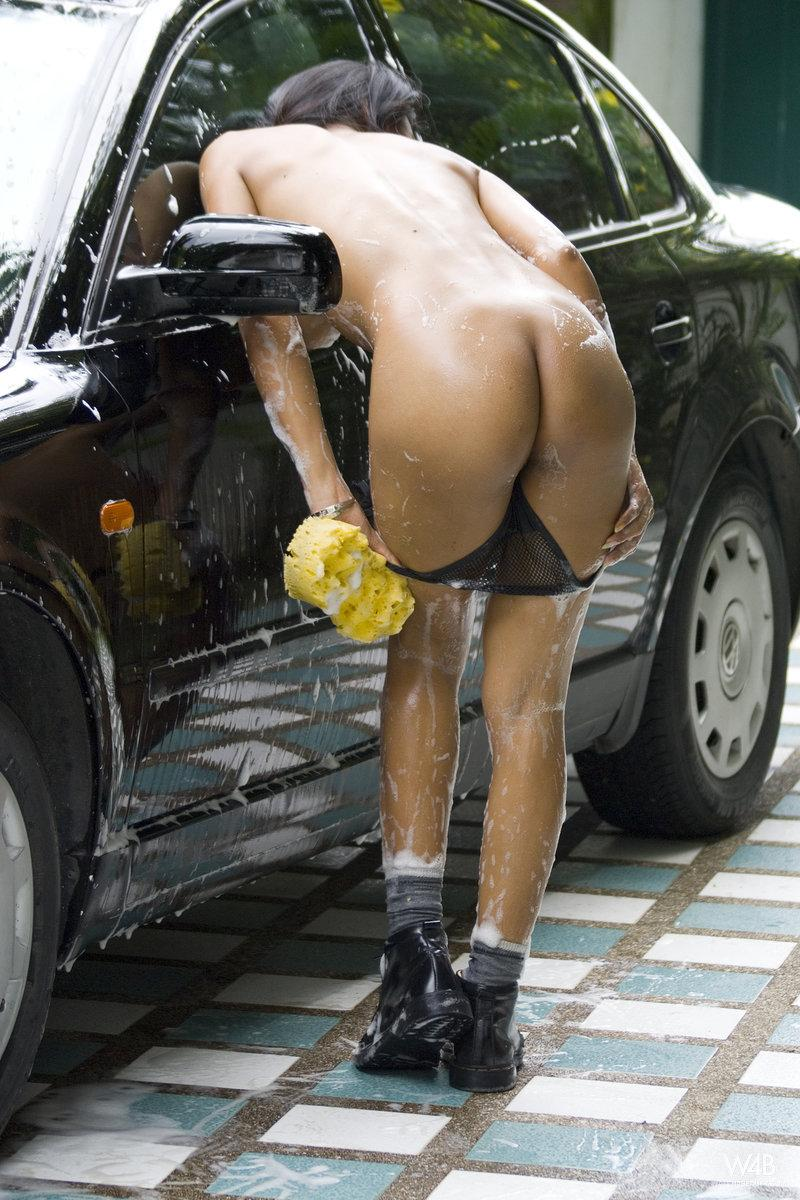Tanned Asian is washing a car - 14