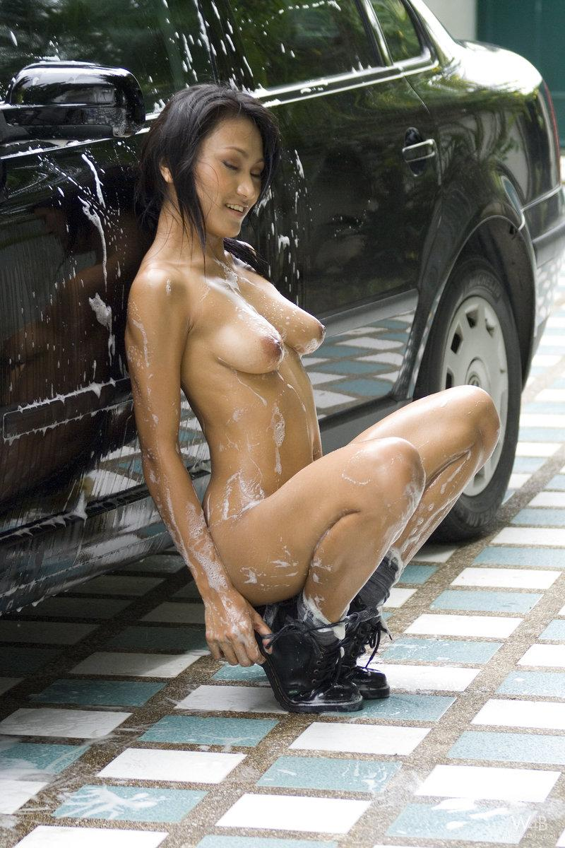 Tanned Asian is washing a car - 15