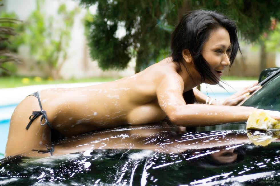 Tanned Asian is washing a car - 2