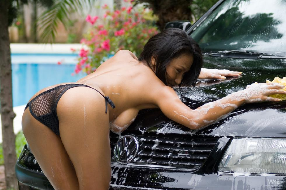 Tanned Asian is washing a car - 4