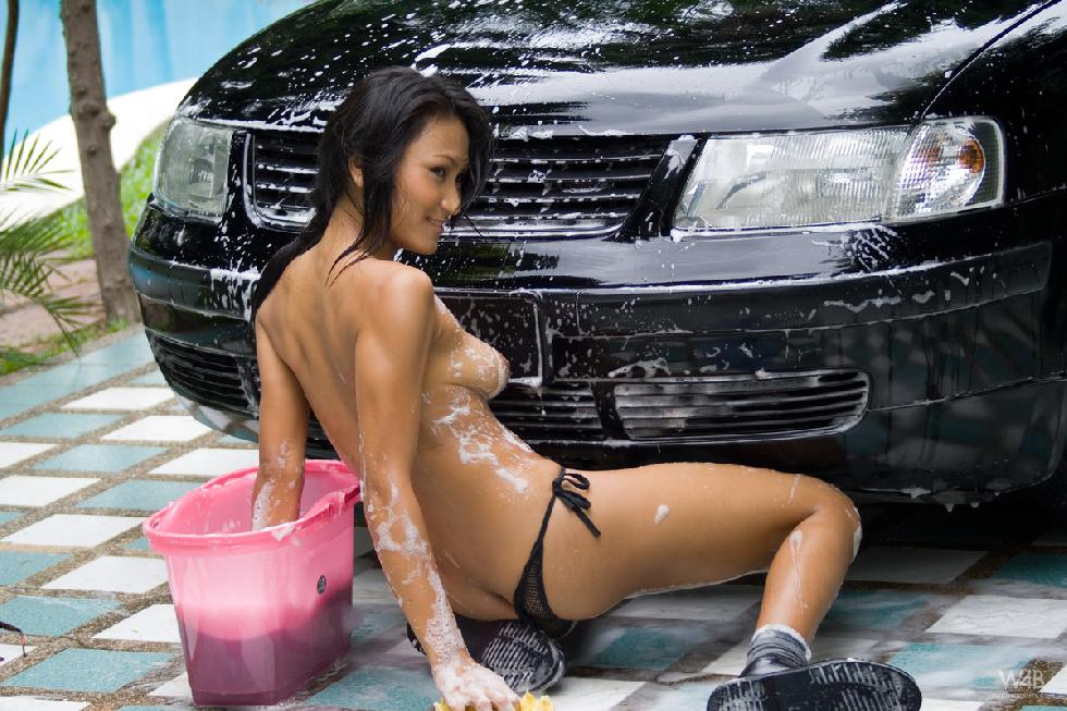 Tanned Asian is washing a car - 7
