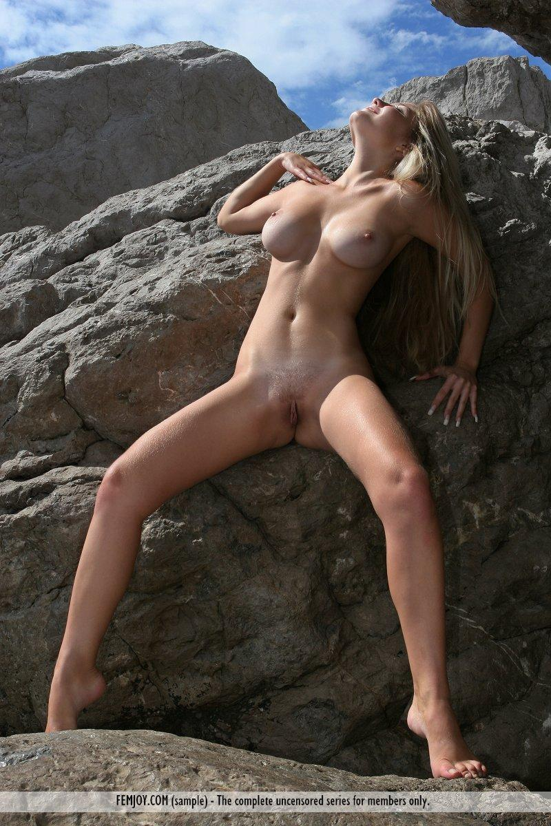 Long-haired Marta is posing naked on the rocks - 1