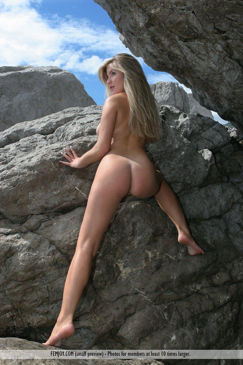 Long-haired Marta is posing naked on the rocks